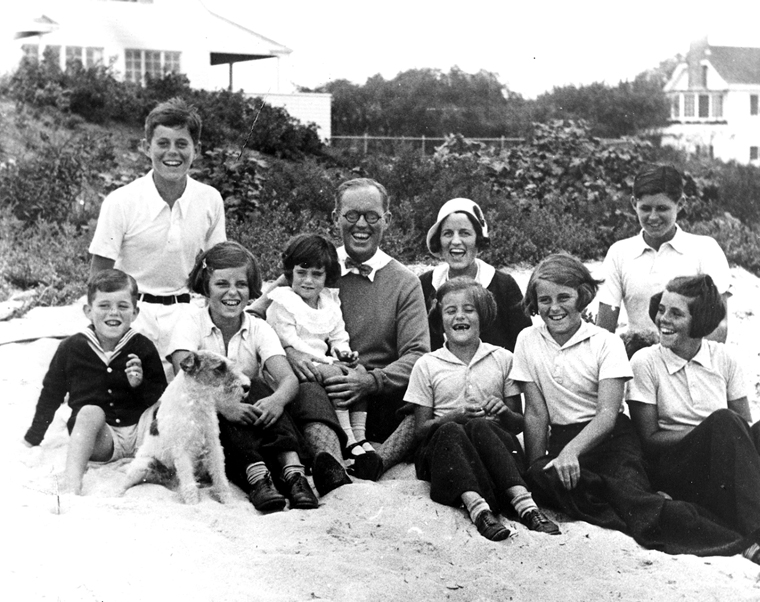 "The Kennedy Family at Hyannis Port, 04 September 1931. L-R: Robert Kennedy, John F. Kennedy, Eunice Kennedy, Jean Kennedy (on lap of) Joseph P. Kennedy Sr., Rose Fitzgerald Kennedy (who was pregnant with Edward ""Ted"" Kennedy at time of this photo), Patricia Kennedy, Kathleen Kennedy, Joseph P. Kennedy Jr. (behind) Rosemary Kennedy. The dog in the foreground is ""Buddy"".(public domain through John F. Kennedy Presidential Library and Museum)"