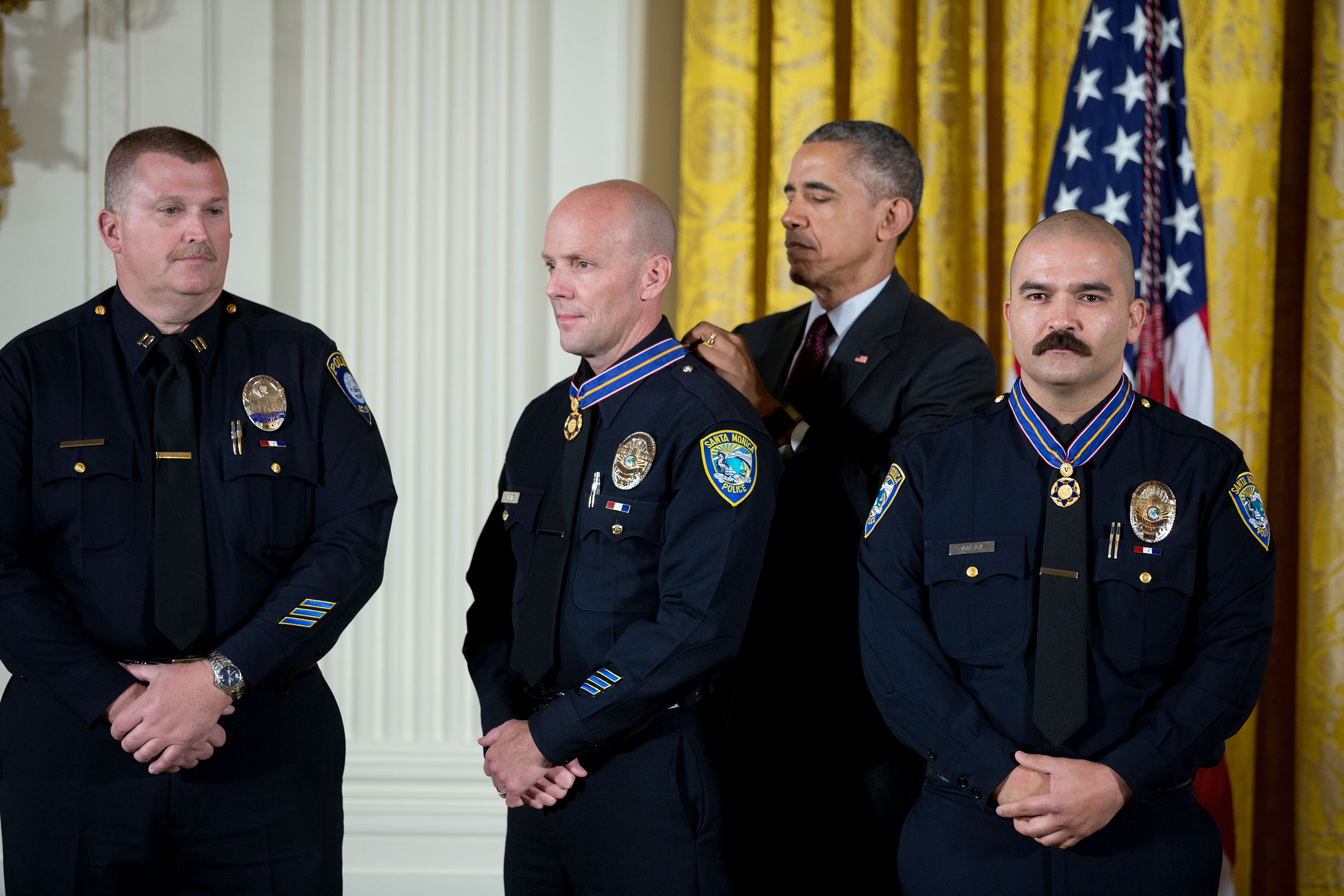 President Barack Obama awards the Medal of Valor to Officer Jason Salas, Officer Robert Sparks, and Captain Raymond Bottenfield of the Santa Monica College Police Department, Calif., during a ceremony in the East Room of the White House, May 16, 2016. The Medal of Valor is awarded to public safety officers who have exhibited exceptional courage, regardless of personal safety, in the attempt to save or protect others from harm. (Official White House Photo By Chuck Kennedy)
